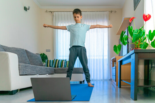 Boy with laptop computer doing sport exercises, practicing yoga at home. Sport, healhty lifestyle, active leisure for kids