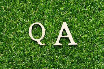 Wood alphabet letter in word QA (abbreviation of quality assurance or question and answer) on green...