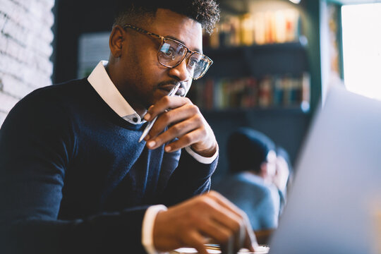 Skilled afro american IT developer in glasses concentrated while coding app for outsourcing cooperating online with testers using laptop computer and free wireless connection in coworking space