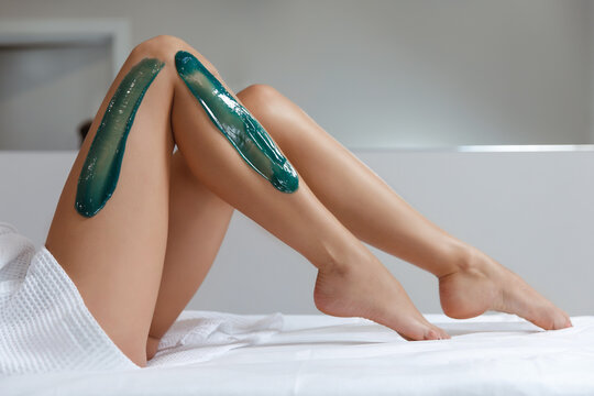 Young woman depilating legs with liquid sugar in spa center