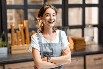 Portrait of a young and happy saleswoman at the counter in ice cream shop or cafe. Concept of a small business and retail