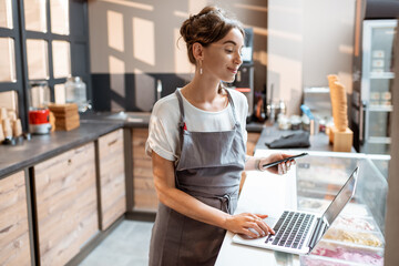 Young saleswoman working with laptop at the counter in ice cream shop or cafe. Concept of a small...