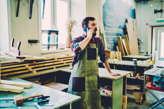 Caucasian craftsman in apron making important cellphone conversation for discussing delivery time of wooden construction to own self employed manufacturing factory, concept of online communication