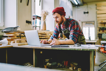 Young hipster guy watching training tutorial on laptop computer learning at carpentry courses, skilled male artisan using netbook for searching information during woodworks and making plannings. Wall mural