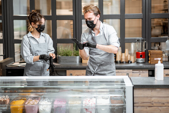 Two sellers in masks and gloves working in the ice cream shop or cafe. Concept of new rules for business during a pandemic