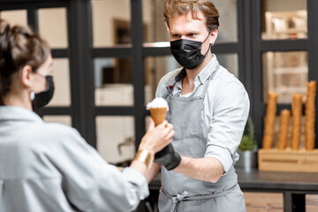 Salesman in protective mask selling ice cream for a young client in the shop. Concept of new social rules for business during a pandemic