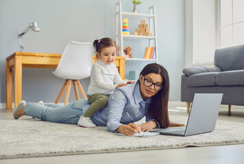 Multitasking for work at home moms. Young woman doing online job on laptop while her daughter...