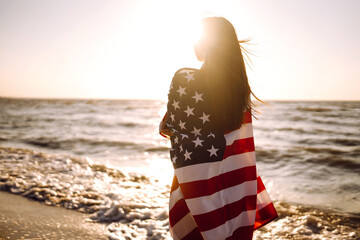 Girl with american flag on the beach at sunset. 4th of July. Independence Day. Patriotic holiday.