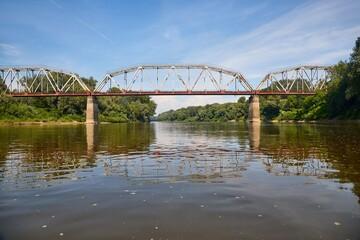 Old railway bridge over a river, rusty metal grid