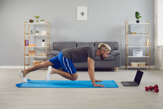 Fit sportsman doing mountain climber exercise online training at home