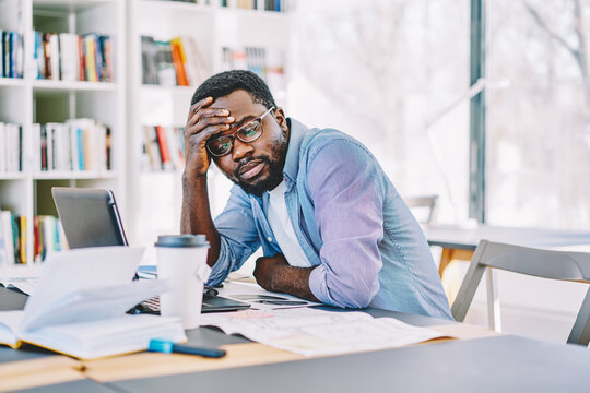Serious african american male student sitting at desktop while watching tutorial on laptop computer tired during exam preparation, unhappy dark skinned freelancer disappointed with doring content  .