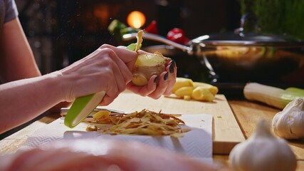 Woman peeling ginger and vegetables for cooking on kitchen table. Closeup hands. Cosy dark room. Real, authentic cooking.