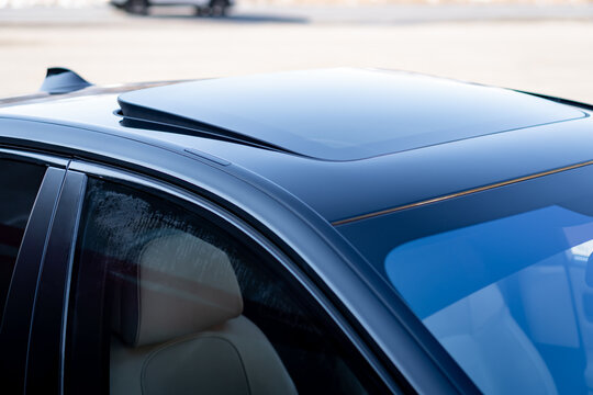 Close up sunroof with wind deflector, black colour. Glazed dach hatch mounted on sedan german car, open for ventilation