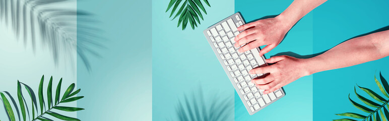 Person using a computer keyboard with tropical leaves and shadow