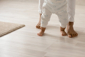 Close up barefoot African American woman with toddler child standing on warm wooden floor with...