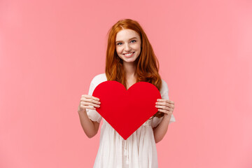 Tenderness, love and romance concept. Romantic charming redhead girlfriend prepared cute gift valentines day, showing red heart card and smiling, express affection and sympathy, pink background