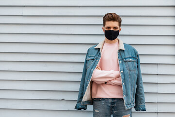 Young handsome fashion man in denim blue fashionable wear and wearing face pollution mask to protect himself from coronavirus in city. Stylish guy model in youth jeans outfit rest on street near wall.