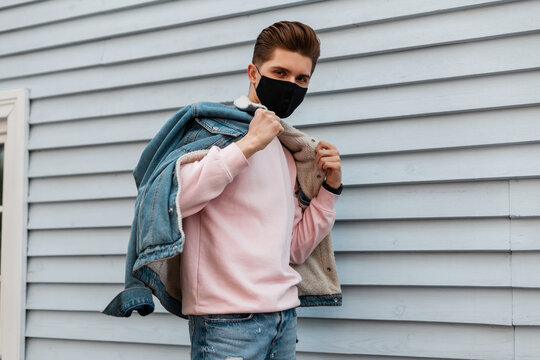 Young man with trendy hairstyle in denim jacket in pink sweatshirt in protective black mask poses near white wall on street. Fashion teenage guy in mask is protected from viruses. Healthy lifestyle.