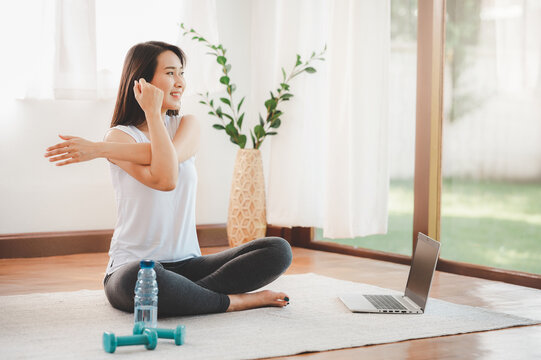Asian woman doing yoga shoulder stretching online class at home