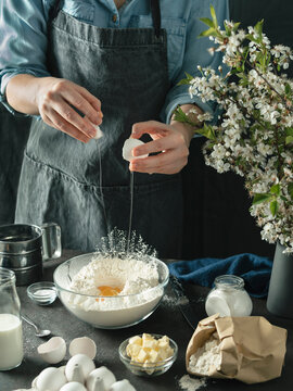 Midsection of woman breaking egg into flour while making bundt cake
