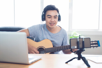Playing guitar writing composing songs using laptop mobile recording music singing live stream social media entertaining people, working at home in living room, wearing headphone listening to audio