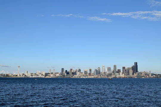 View of Seattle from Alki Beach in West Seattle over the Puget Sound; wide panoramic view of the city with a few small boats in between on the water.