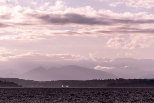 View towards the Olympic Mountains across from Alki Beach in West Seattle on a late summer day. There are dramatic clouds over the Sound.