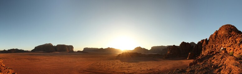 Scenic panoramic view of the famous Wadi Rum desert in Jordan. Image features the red sands and rock formations across at a wide angle. Image taken at sunset as sun vanishes behind the mountains.