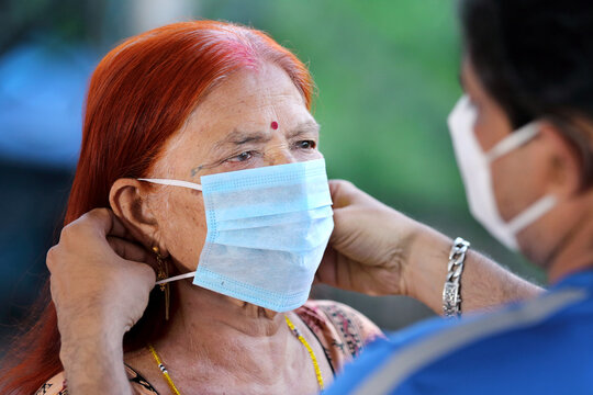 Indian son helping old mother wearing face mask to prevent covid-19. Son taking care of old mother during corona virus pandemic. Teaching to wear mask properly. How to wear face mask.