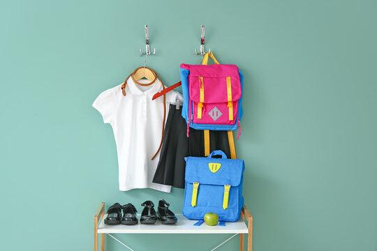 Stylish school uniform with backpacks near color wall