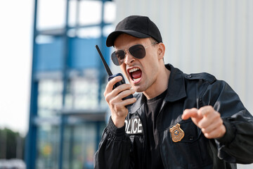 Aggressive police officer with two-way radio outdoors