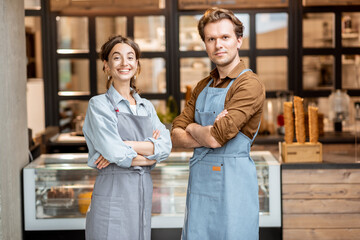 Portrait of a two cheerful employees of a cafe or small shop standing in front of the counter inside