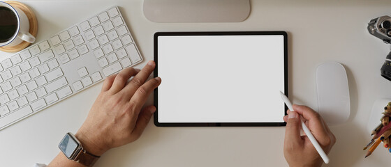 Businessman using blank screen tablet with stylus on white office desk with computer device and...