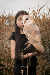 Portrait of girl holding barn owl