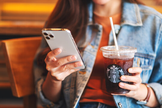 Jun 16th 2020 : A woman holding and using Iphone 11 Pro Max smart phone while drinking iced coffee at Starbucks coffee shop , Chiang mai Thailand