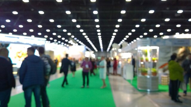Abstract blur people in trade show background. New modern exhibition, convention and conference expo centre. Venue for holding business. Financial and economic growth and crisis concept. Collaboration