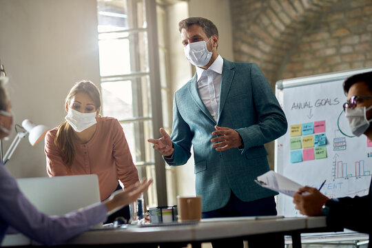 Businessman wearing protective face mask while talking on a meeting in the office.