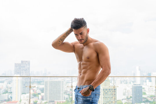Young handsome muscular Persian man shirtless and looking down against view the city