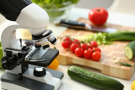 Close up of laboratory optical microscope, rope tomatoes, cucumbers, knife and wooden cutting board on desk