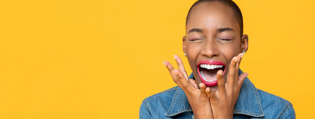 Panoramic close up portrait of ecstatic young African American woman screaming with hands covering face isolated studio yellow background