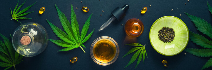 Medical CBD oil on black trendy background with cannabis leaves. The concept of medical tincture of...