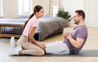 Girlfriend Sitting On Boyfriends Legs Helping Him Exercise At Home