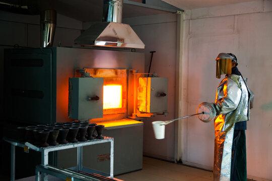 Gold melting. Taking metal sample. Metallurgy lab of golden manufacturing plant.