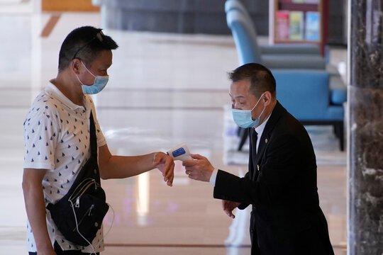 A member of management staff takes the body temperature of a woman entering a hotel in Shanghai