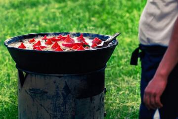 Cook prepares Uzbek Pilaf with paprika, outdoors