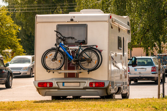 Two pleasure bikes are strapped to the back of the camper van