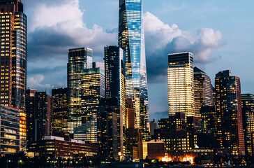 Fotomurales - Scenery view of Lower Manhattan skyline at evening with city lights in windows. Beautiful cityscape view of New York downtown. Contemporary metropolis city in need of a huge amount of electricity