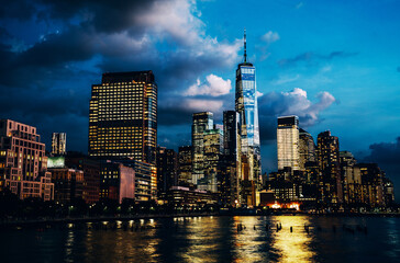 Fotomurales - Scenery view of Lower Manhattan skyline at evening with city lights reflected in Hudson river. Beautiful New York cityscape view. Contemporary metropolis city in need of a huge amount of electricity