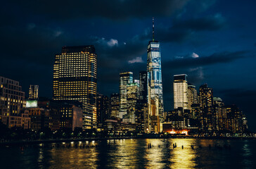 Fotomurales - Scenery view of Lower Manhattan skyline at night with city lights reflected in Hudson river. Beautiful New York cityscape view. Contemporary metropolis city in need of a huge amount of electricity