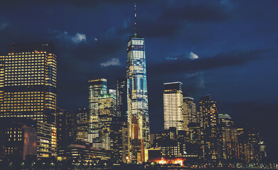 Fotomurales - Scenery view of Lower Manhattan skyline at night with city lights in windows. Beautiful cityscape view of New York downtown. Contemporary metropolis city in need of a huge amount of electricity